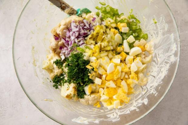 Cauliflower potato salad ingredients in a glass mixing bowl