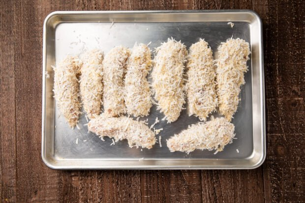 Battered coconut chicken strips on baking sheet