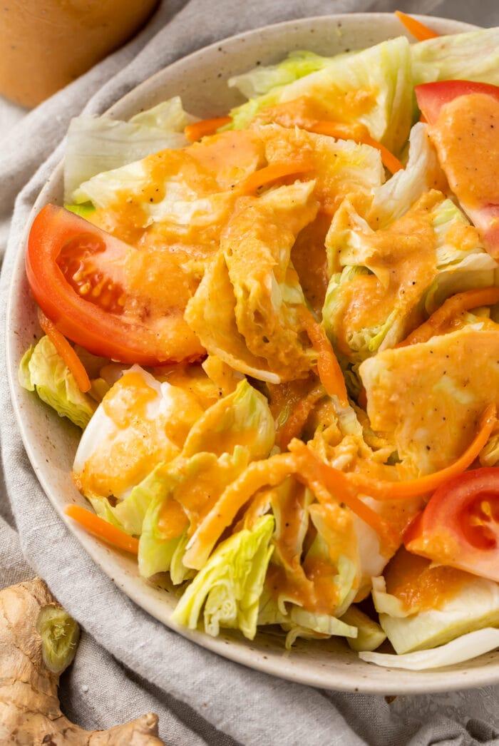 Ginger salad dressing on a salad in a bowl