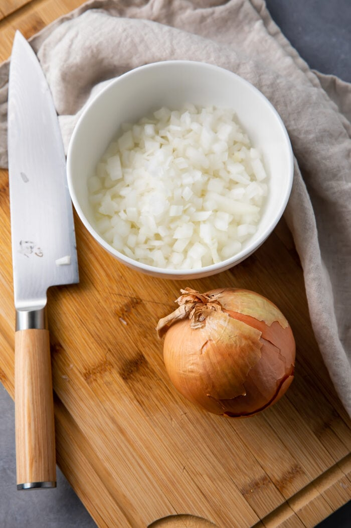 A whole onion next to a bowl of diced onion and a knife on a cutting board with a dish towel