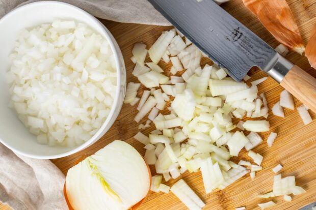 Diced onion on a cutting board next to a bowl of diced onion and a sharp knife