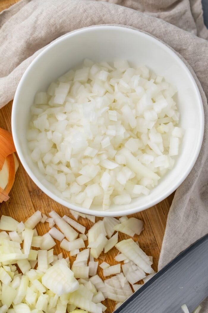 Diced onion on a cutting board next to a bowl of diced onion