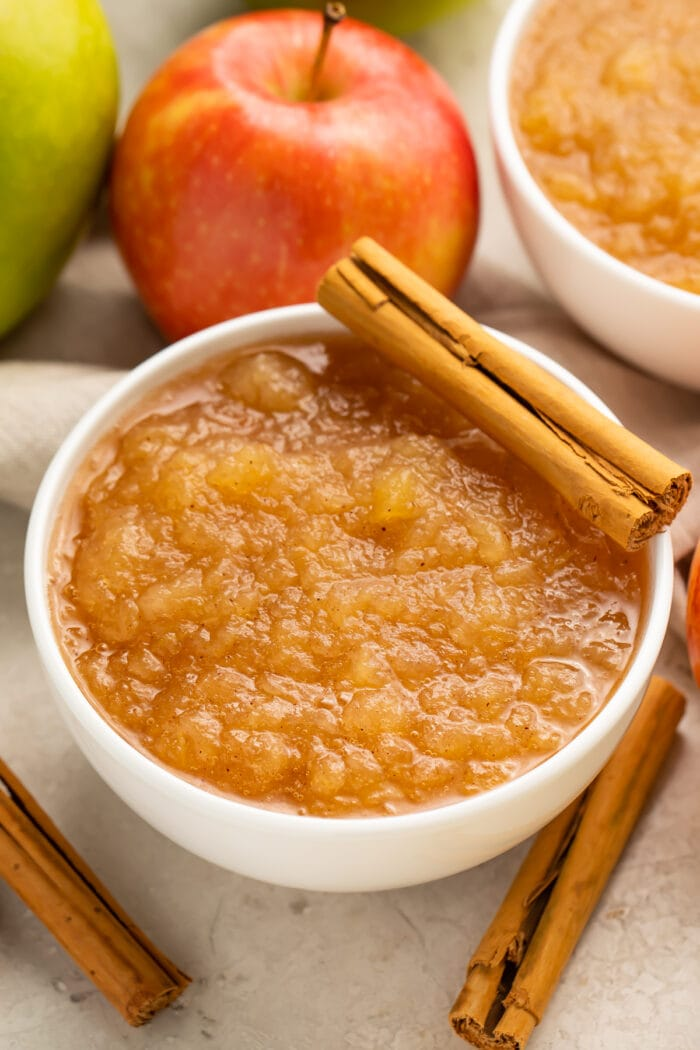 Instant Pot applesauce in a large bowl surrounded by apples and topped with a whole cinnamon stick