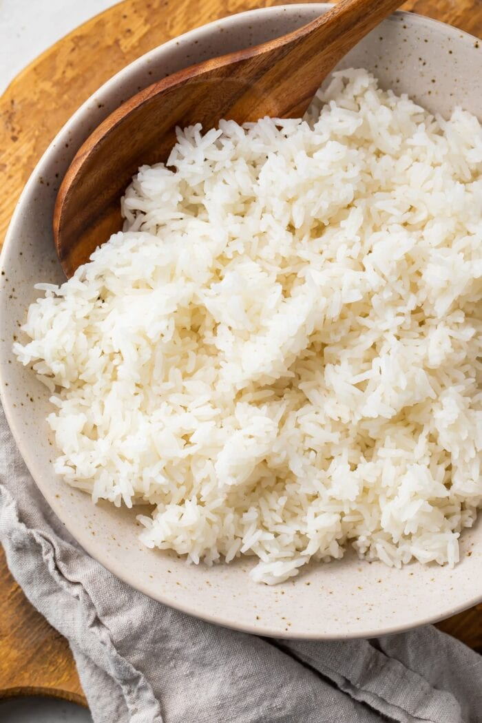 Overhead photo of Instant Pot jasmine rice in a bowl on a wooden tray with a cloth napkin