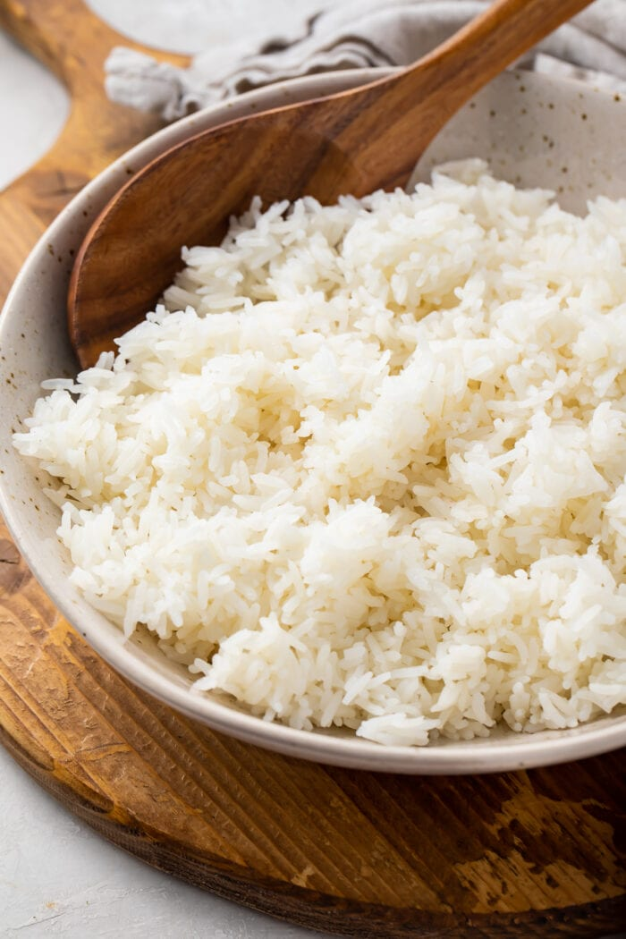 Angled photo of Instant Pot jasmine rice with a wooden spoon in a large bowl on a wooden tray with a cloth napkin