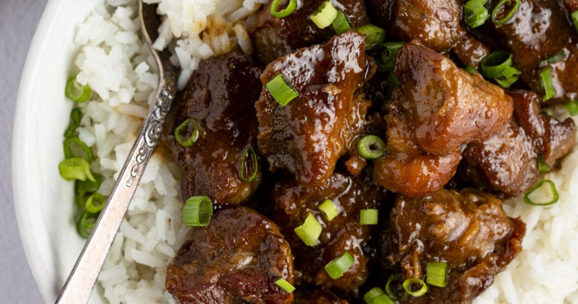 Pork adobo on top of white rice in a serving bowl