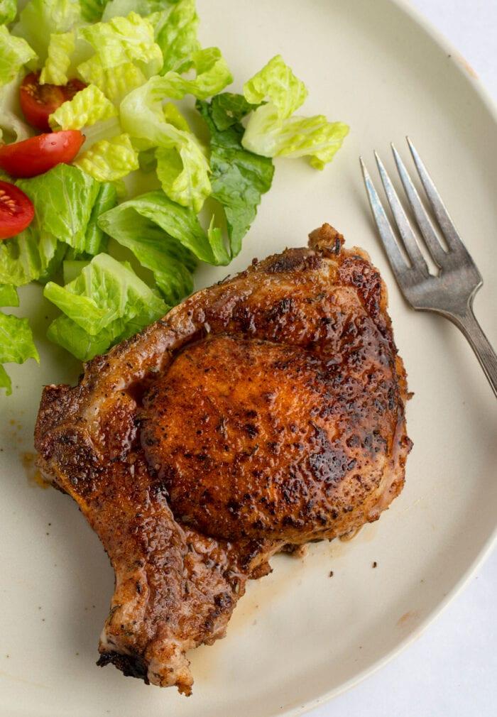 Pork chop with pork chop seasoning on plate next to salad