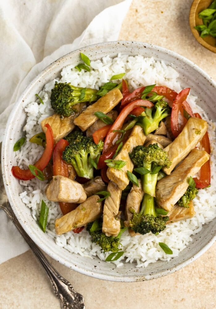 Pork stir fry on a bed of white rice in a white bowl with a napkin and spoon off to the side