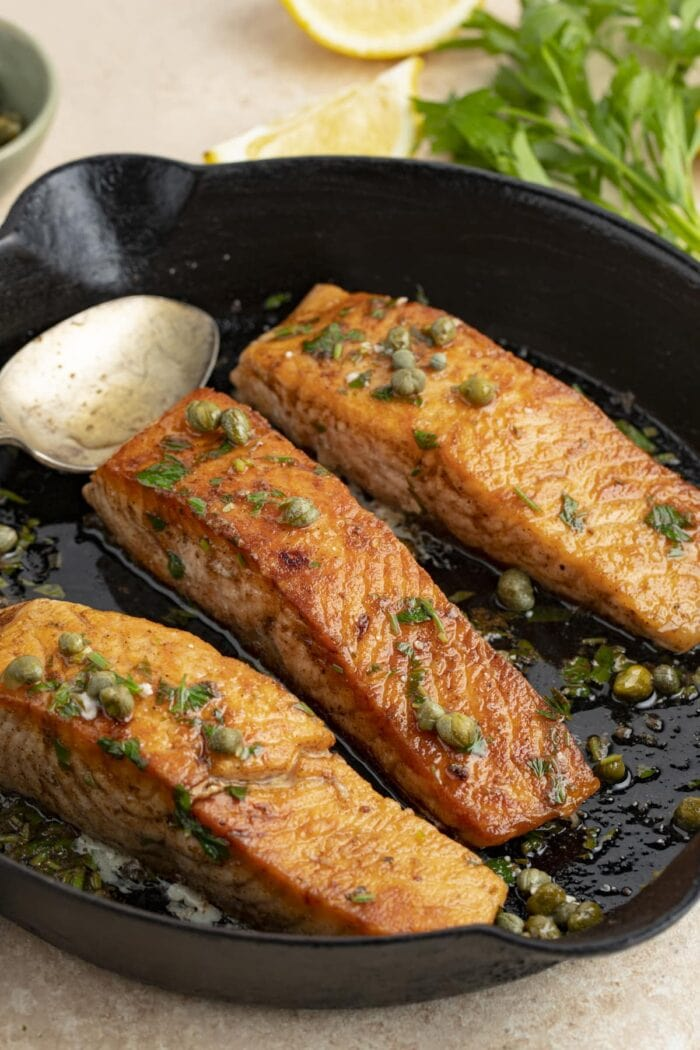 3 salmon meuniere fillets in a cast iron skillet with parsley and lemon wedges in the background