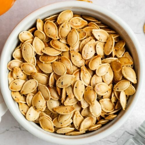 air fryer pumpkin seeds in a dish with a pumpkin on the side