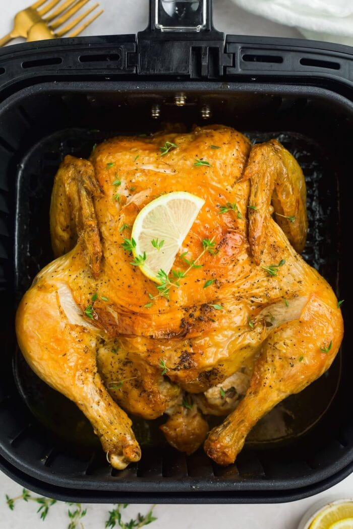 air fryer whole chicken in air fryer basket with a lemon slice and fresh thyme on top