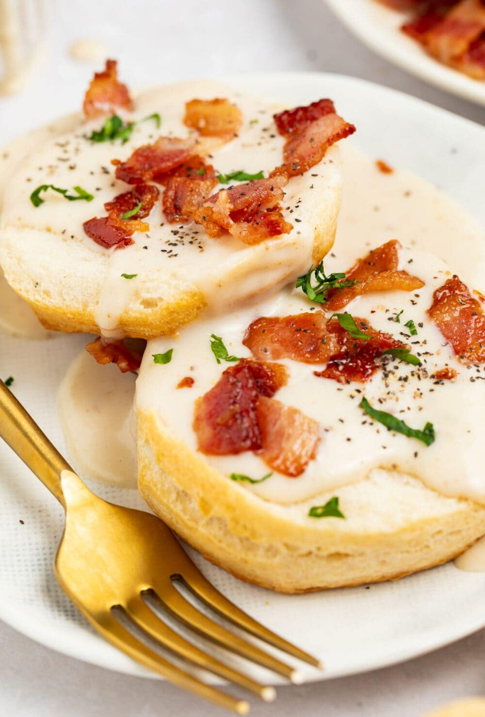 bacon gravy on biscuits with bacon pieces and chopped parsley on top