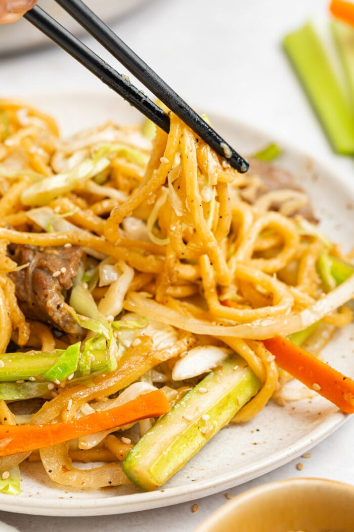 beef chow mein being lifted off a plate with chopsticks