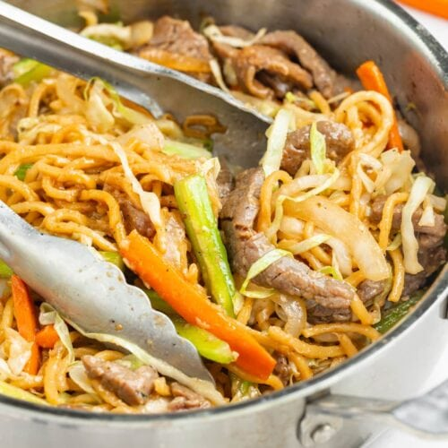 beef chow mein in a skillet with tongs