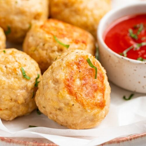 close-up image of baked chicken meatballs on a plate with tomato sauce on the side