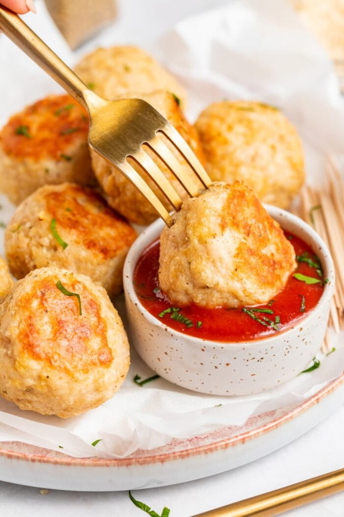 baked chicken meatballs being dipped into tomato sauce