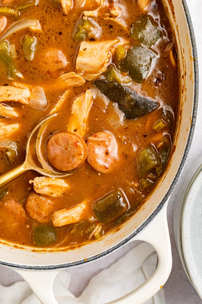 chicken and sausage gumbo in a large pot with a spoon