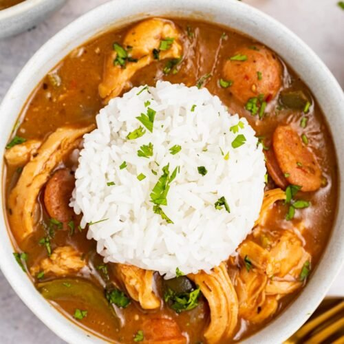 chicken and sausage gumbo in a bowl with a scoop or rice on top