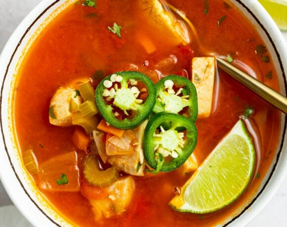 overhead image of a bowl of mexican chicken soup with sliced jalapenos and a lime wedge on top