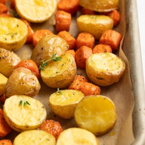 roasted potatoes and carrots on a baking sheet with fresh thyme on top