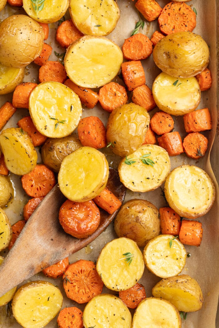 roasted potatoes and carrots on a baking sheet with fresh thyme on top and a wooden spoon