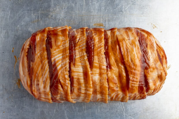 Bacon wrapped meatloaf on baking sheet