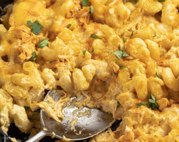 Buffalo chicken mac and cheese in a cast iron skillet with a spoon