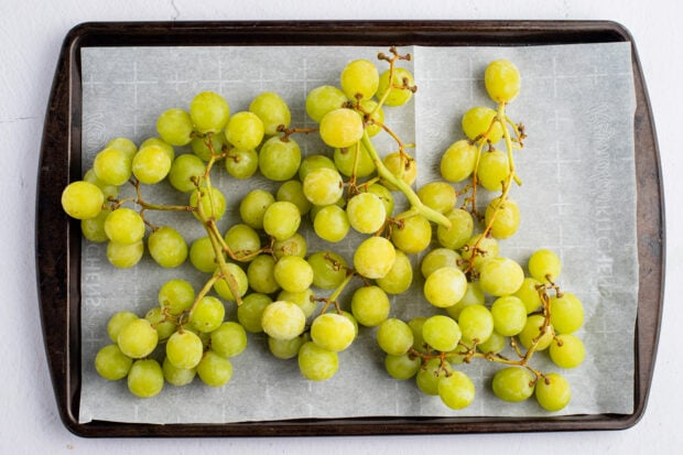 Green grapes on a baking sheet lined with parchment paper