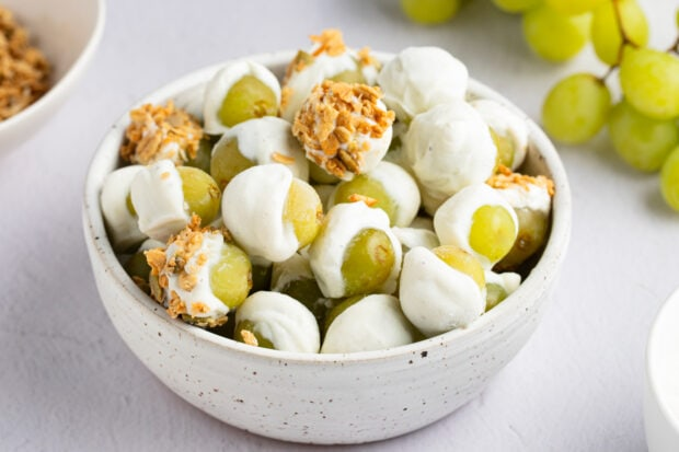 Frozen yogurt-covered grapes with granola in a bowl