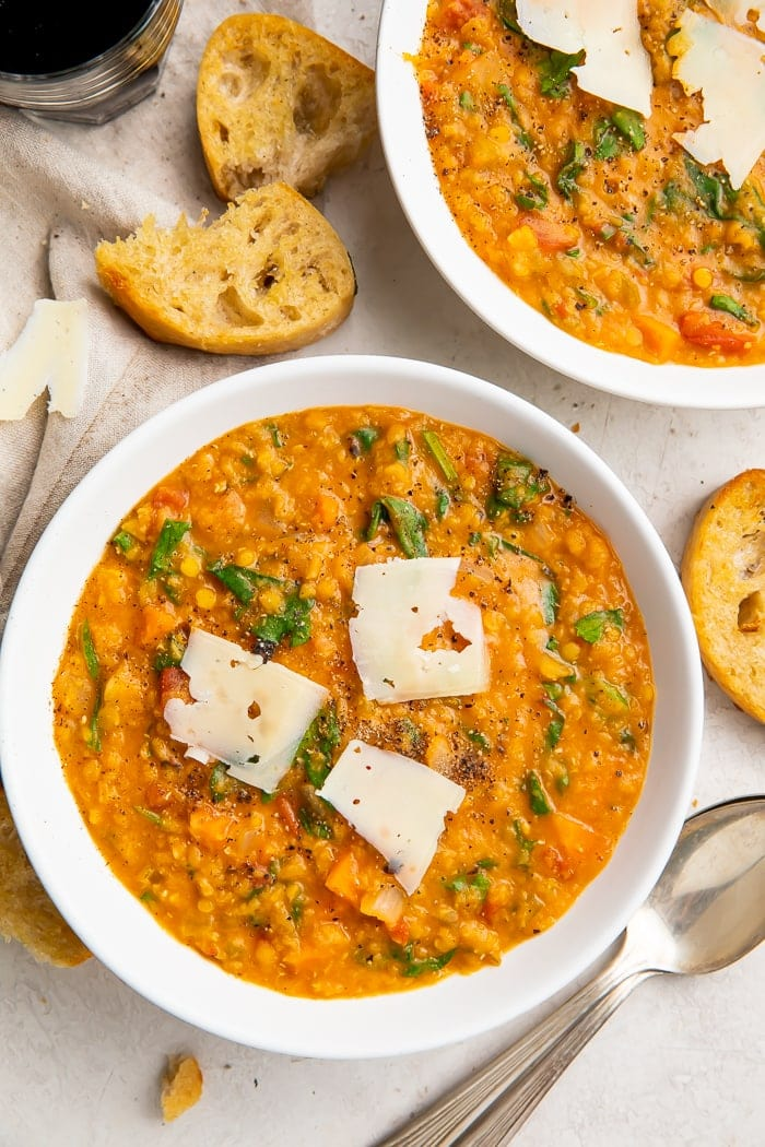 Overhead, zoomed out photo of Instant Pot lentil soup in white bowls, surrounded by crusty bread