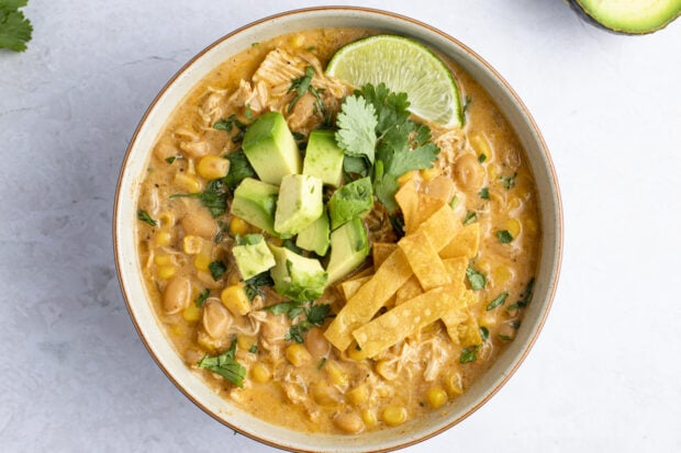 Instant Pot white chicken chili in a bowl with diced avocado, cilantro, and lime on top