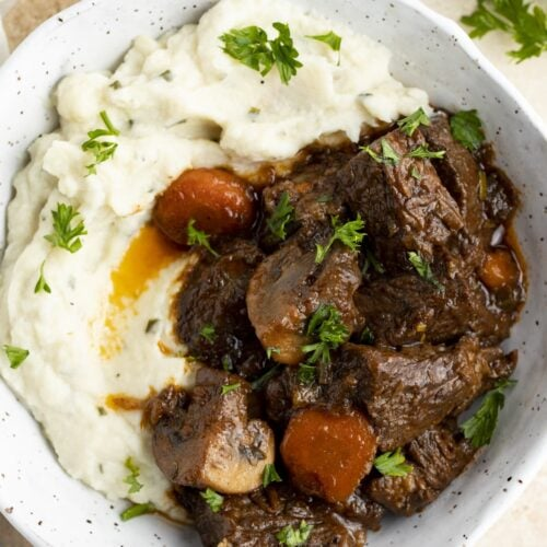 Overhead view of keto beef stew in a bowl with mashed cauliflower