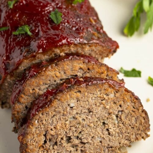 Slow cooker meatloaf, photographed from an overhead angle, with two slices leaning up against the end of the loaf on a white plate