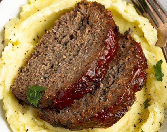 2 pieces of slow cooker meatloaf on a bed of mashed potatoes