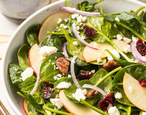 Spinach salad in a large bowl with another bowl of spinach salad in the background