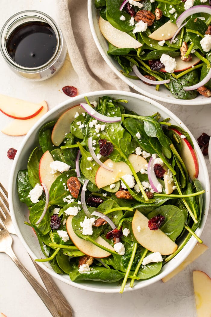 Zoomed out overhead photo of spinach salad in bowls