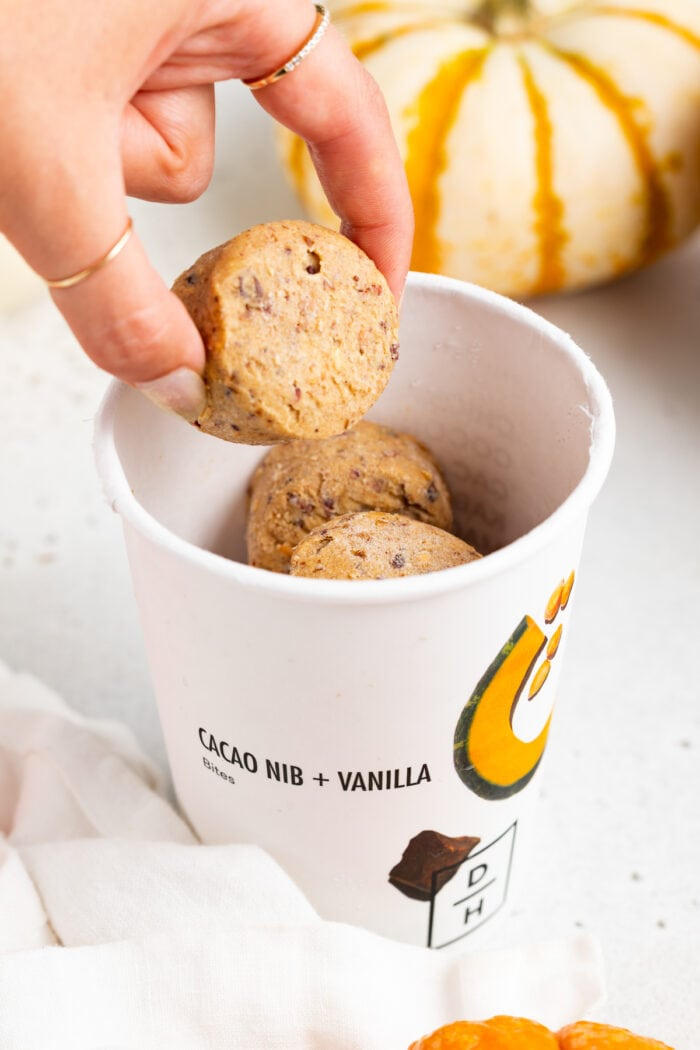 Daily Harvest bites in a paper cup. A hand picks up one bite out of the cup