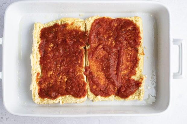 Marinara sauce on dinner rolls in baking dish