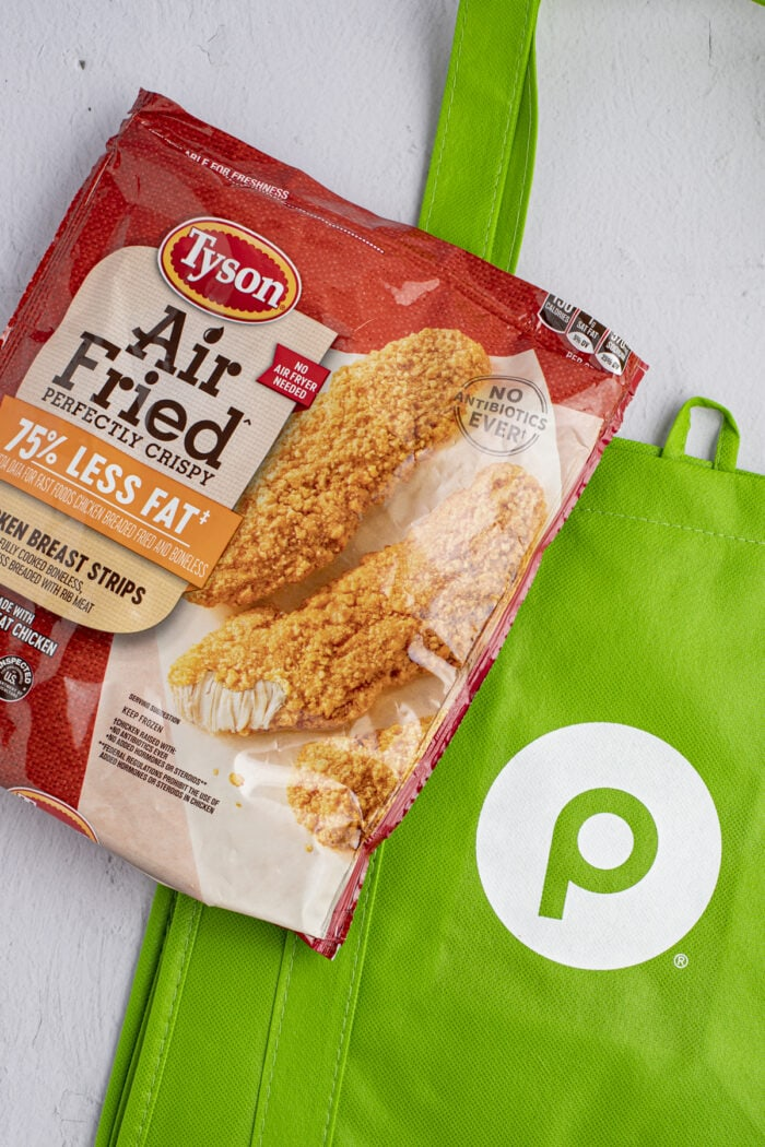 Tyson air fried chicken strips packaging with a Publix reusable shopping bag