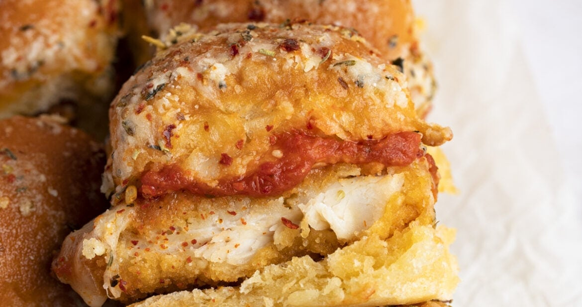 Crispy chicken parm sliders, with one slider laying on top of the others at an angle to show chicken and marinara inside