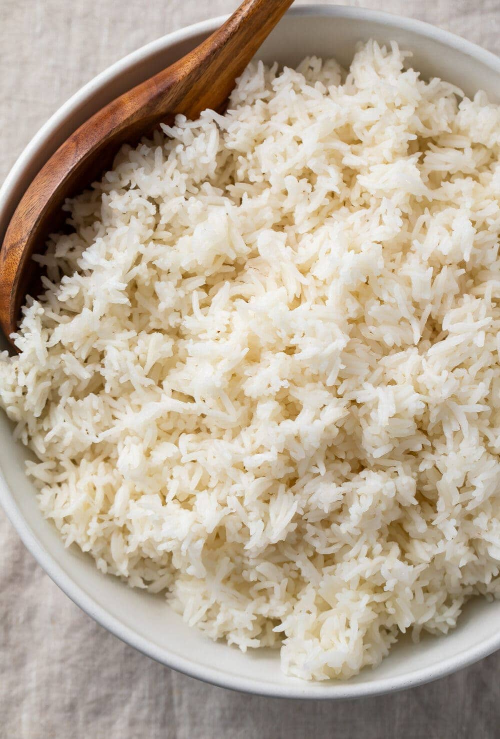 Overhead view of a large bowl of Instant Pot basmati rice with a wooden spoon on a table