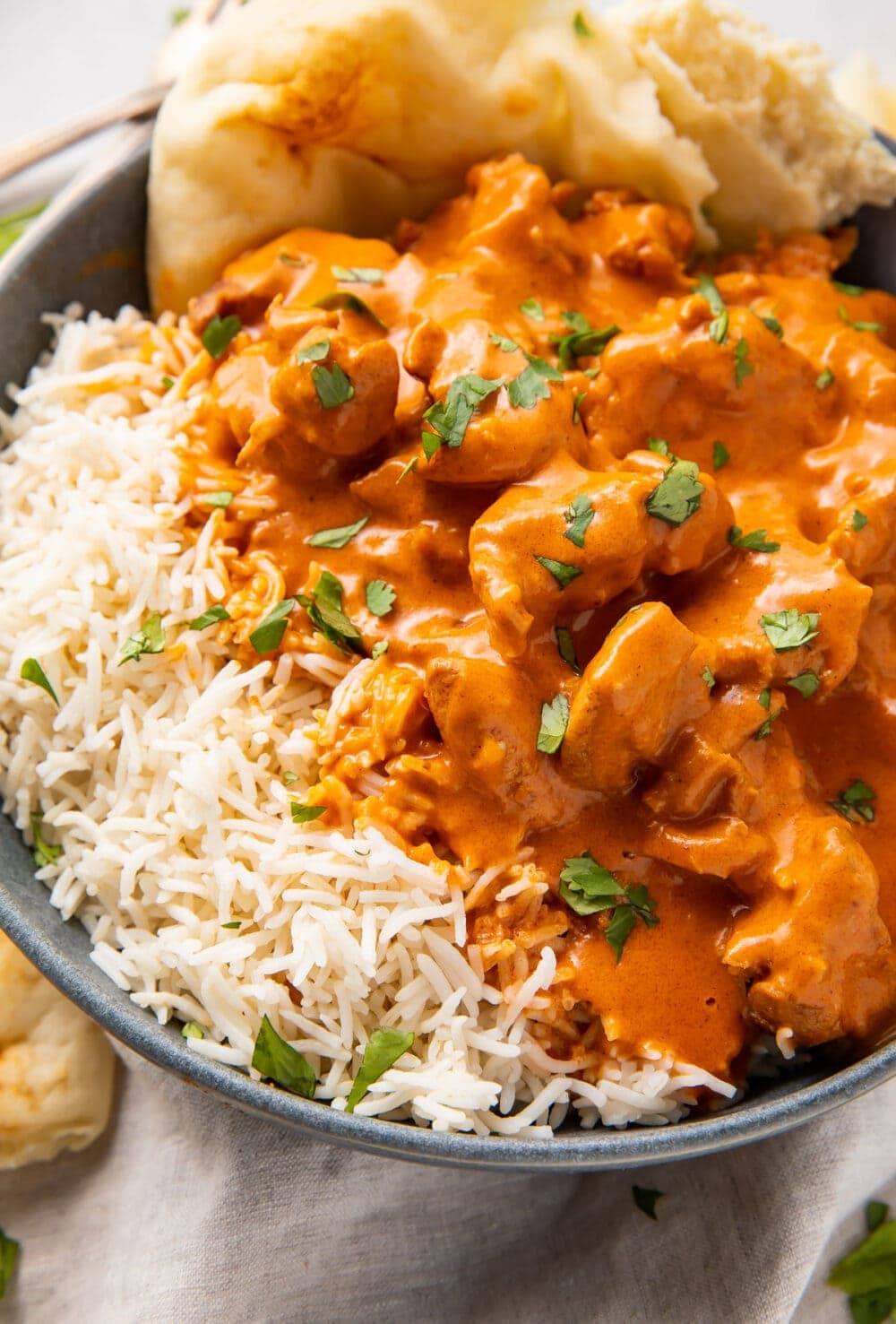 Instant Pot butter chicken, steamed basmati rice, and naan in a large grey bowl
