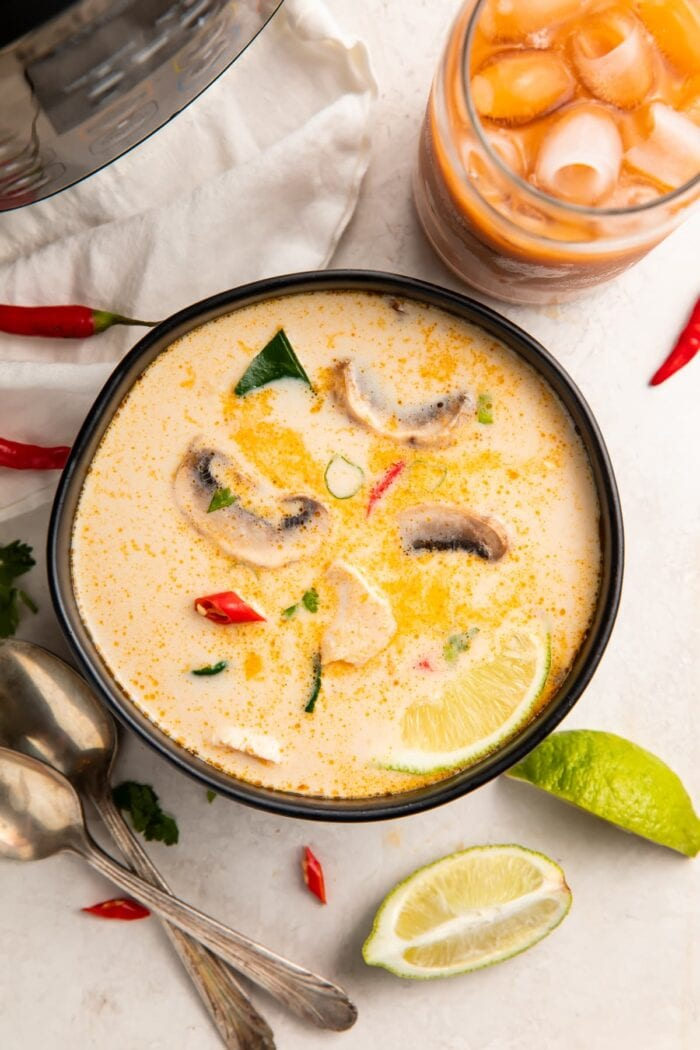 Overhead view of Instant Pot tom kha soup in a black bowl surrounded by limes and peppers