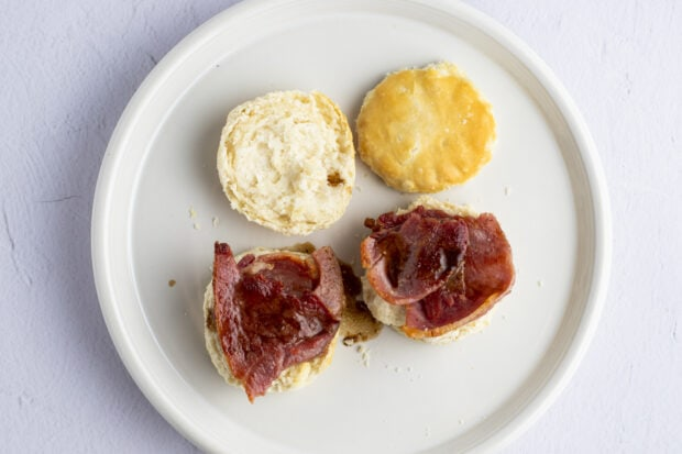 Ham and biscuits with red eye gravy on white plate