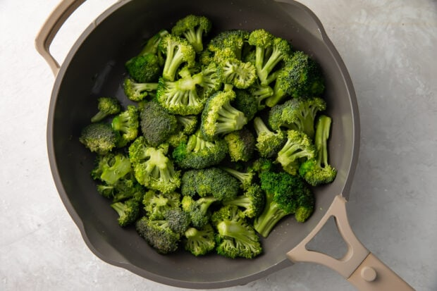 Sauteed broccoli in a large grey skillet